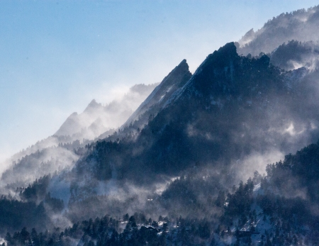 Snow billowing off of the Boulder Flatirons